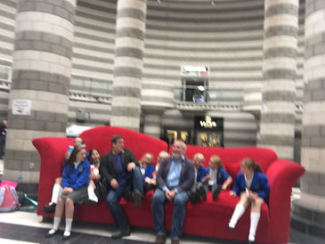 Chris Riddell and Paul Cookson with pupils on the big red sofa